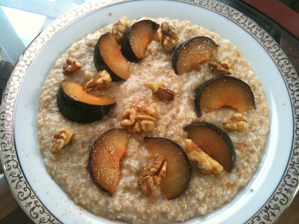 Steel cut oats with plum, freshly grated cinnamon, maple syrup, and walnuts